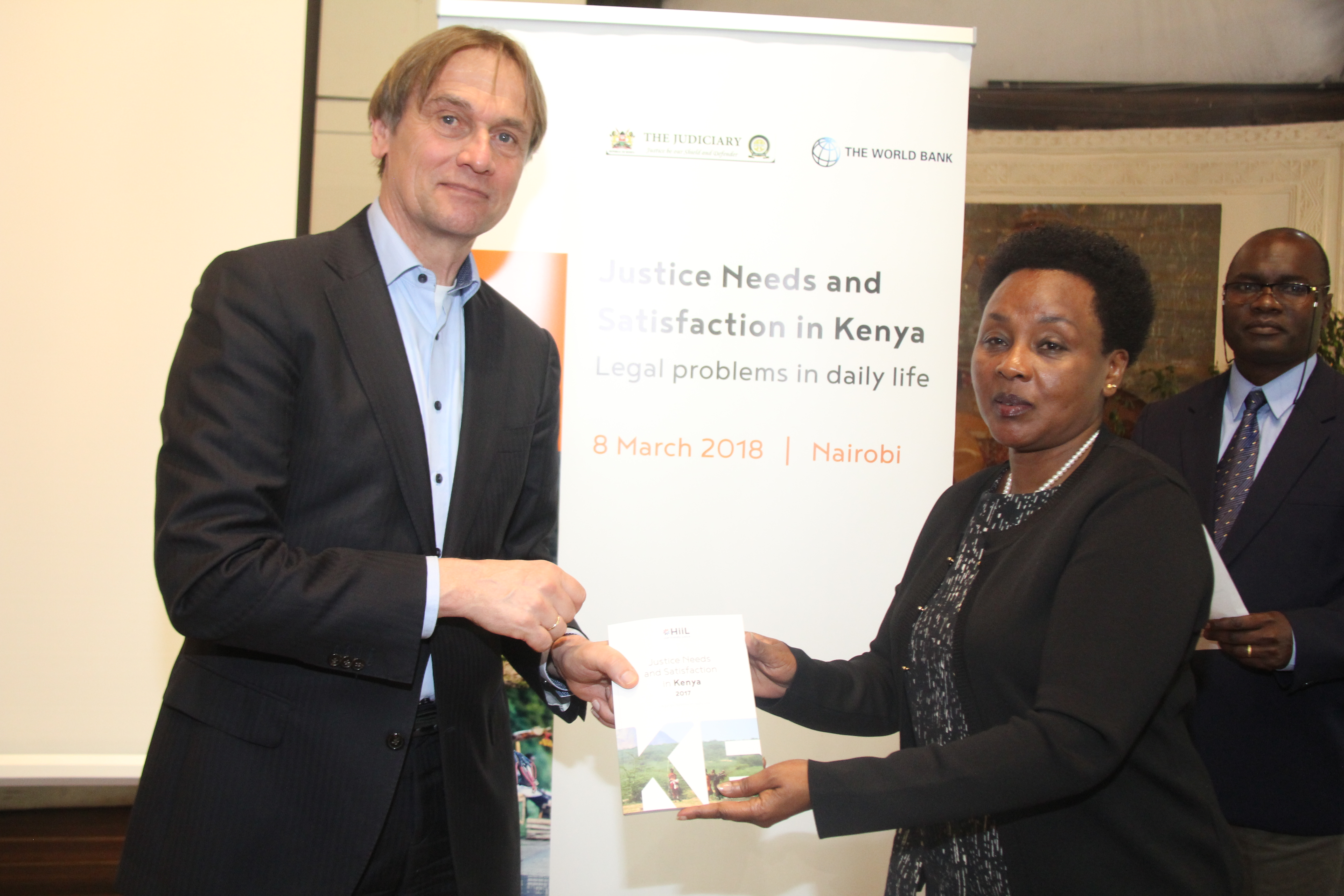 Deputy Chief Justice Philomena Mwilu receiving the JNS report from Mauritis Barendrecth,  Research Director, The Hague Institute for Institutionalization of Law (HiiL).